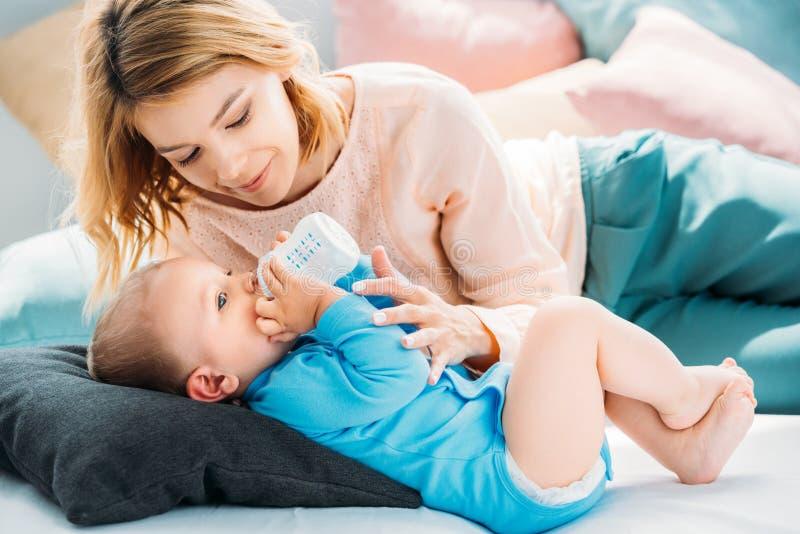Mutter, die ihr kleines Kind mit Babyflasche auf Bett einzieht stockfoto