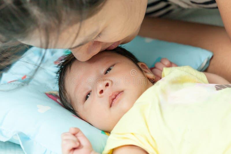Mutter, die ihr neugeborenes Baby des Sohns küsst stockfoto
