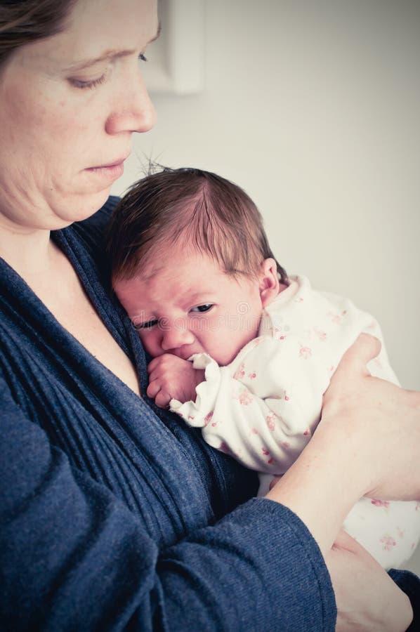 Mutter, die ihr neugeborenes Baby hält lizenzfreie stockbilder