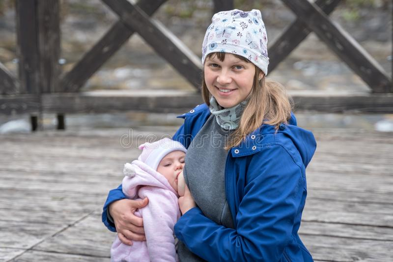Mutter, die ihr neugeborenes Baby im Park stillt lizenzfreie stockfotografie