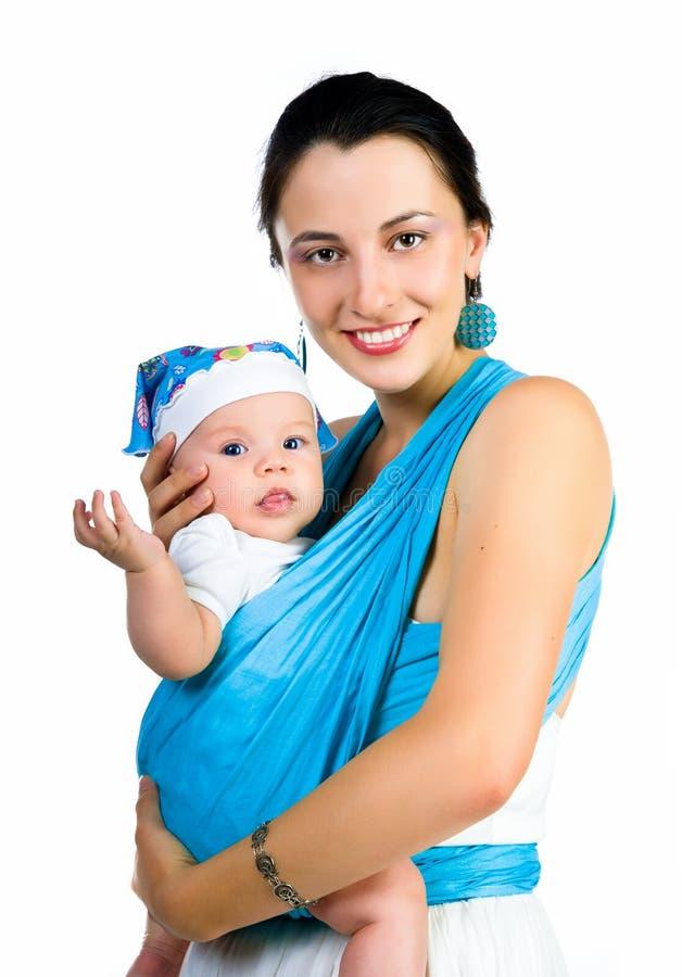 Mutter, die ihr Schätzchen in einem Riemen trägt lizenzfreies stockbild
