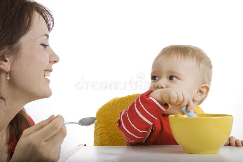 Mutter, die ihr Schätzchen speist lizenzfreies stockbild