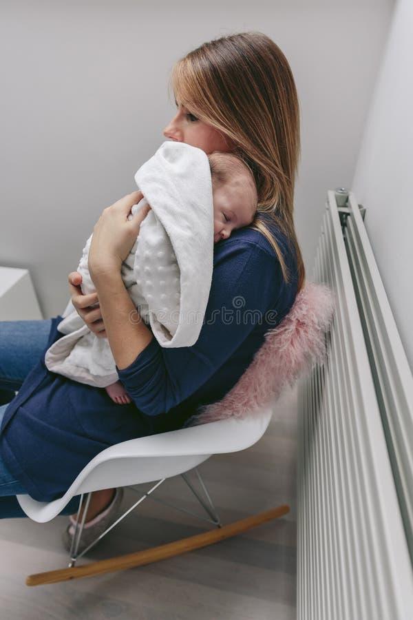Mutter, die ihr schlafendes Baby umarmt lizenzfreie stockfotografie