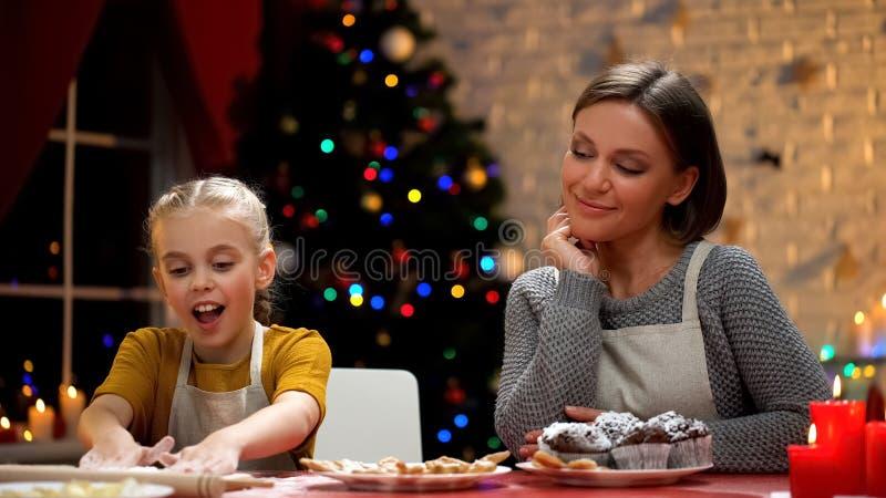 Mutter, die ihre aufgeregte Tochter zubereitet Plätzchen für Weihnachtsessen betrachtet lizenzfreies stockbild