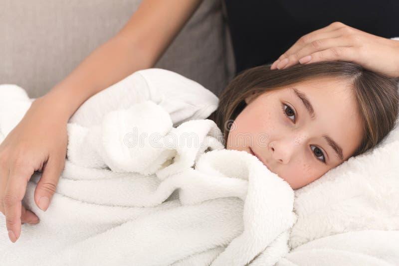 Mutter, die ihre Tochter, liegend auf Mutterknien streicht lizenzfreie stockfotografie