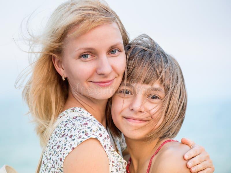 Mutter, die ihre Tochter umarmt lizenzfreie stockbilder