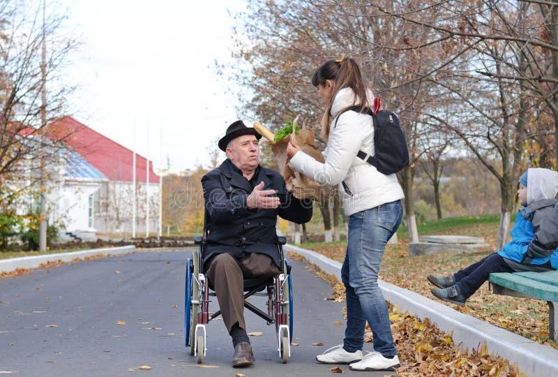 Mutter, die ihrem älteren behinderten Vater hilft stockbild