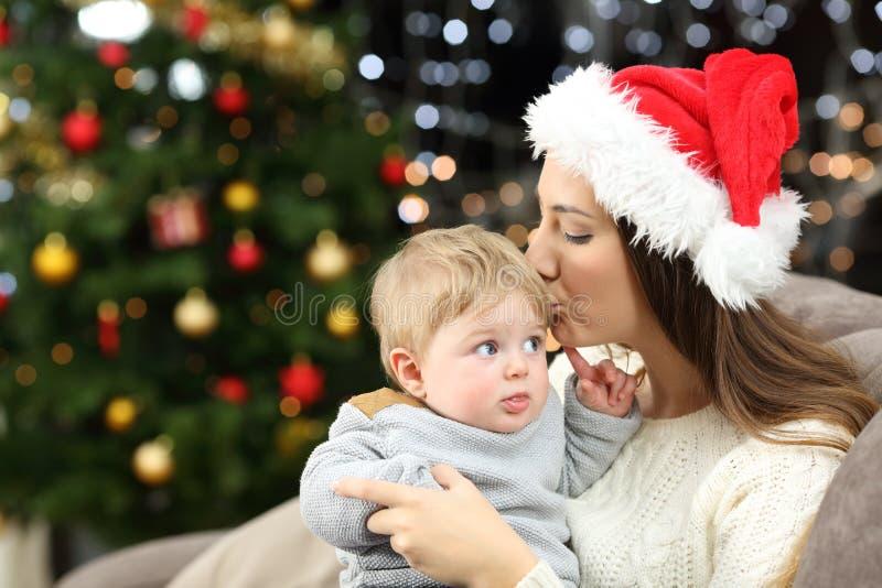 Mutter, die ihren Babysohn im Weihnachten küsst stockfotografie