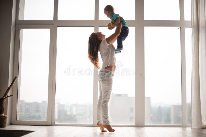 Mutter, die ihren kleinen Jungen in der Luft hält stockfotografie