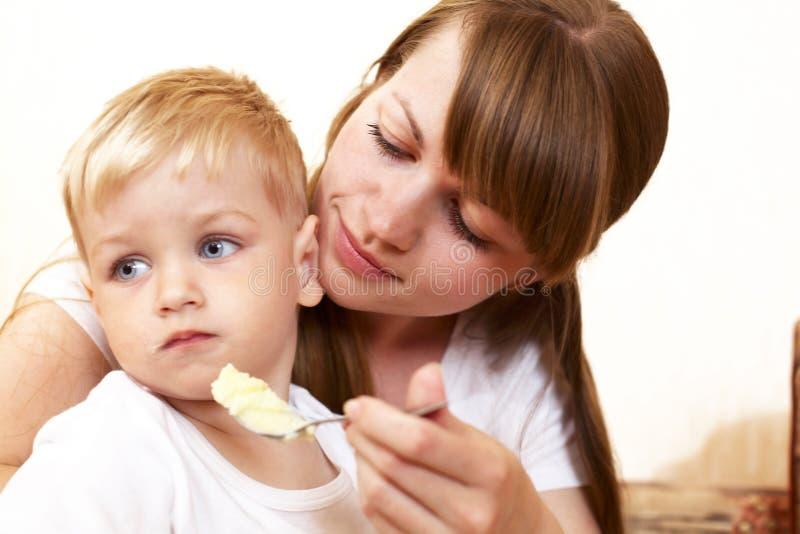 Mutter, die ihren Sohn speist stockfoto