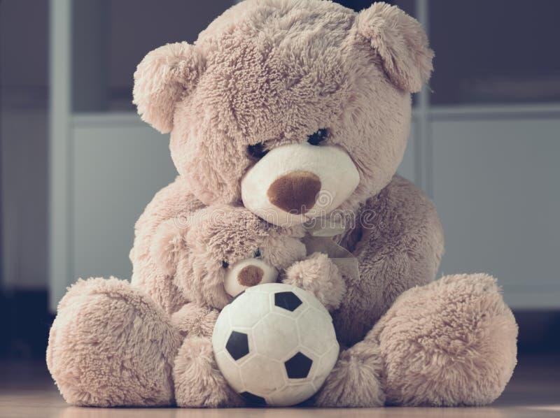 Mutter, die ihren Sohnteddybären mit Ball umarmt stockbild