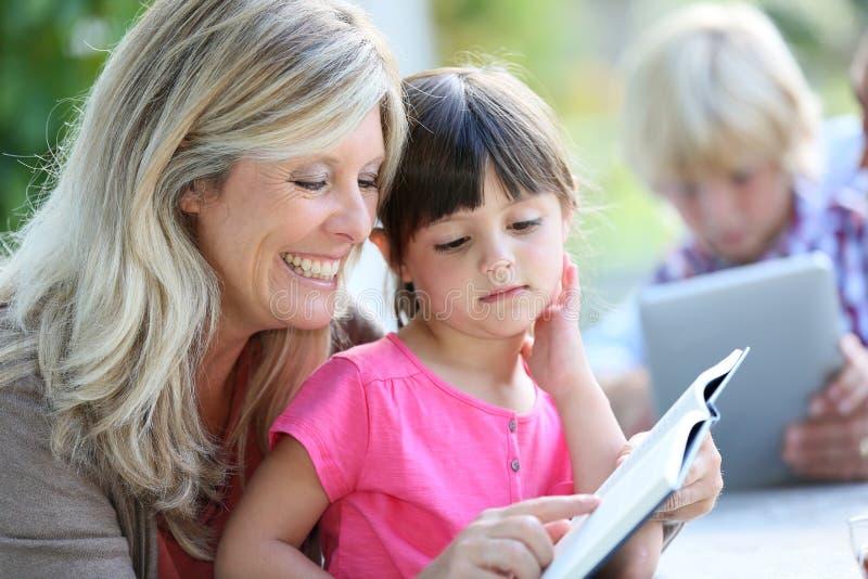 Mutter, die ihrer Tochter beibringt, wie man liest lizenzfreie stockbilder