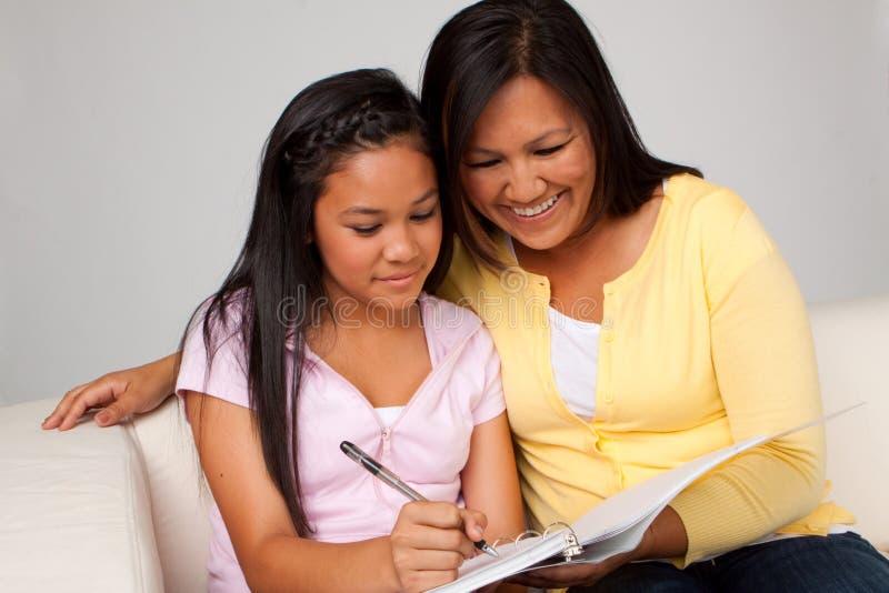 Mutter, die ihrer Tochter mit Heimarbeit hilft lizenzfreie stockfotografie