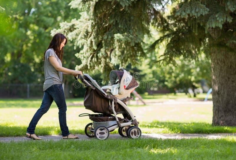 Mutter, die Kinderwagen im Park drückt stockbild