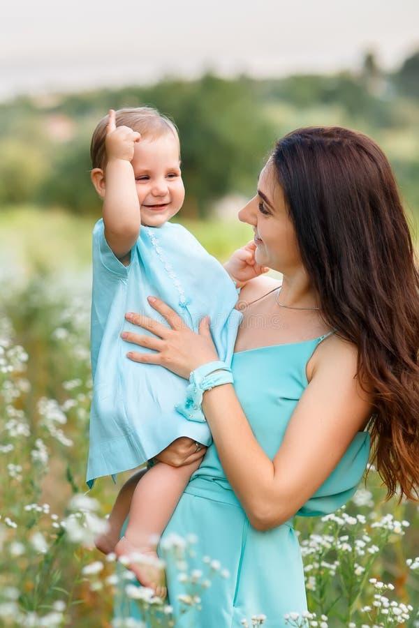 Mutter, die kleine Tochter auf Sommerwiese hält stockfoto