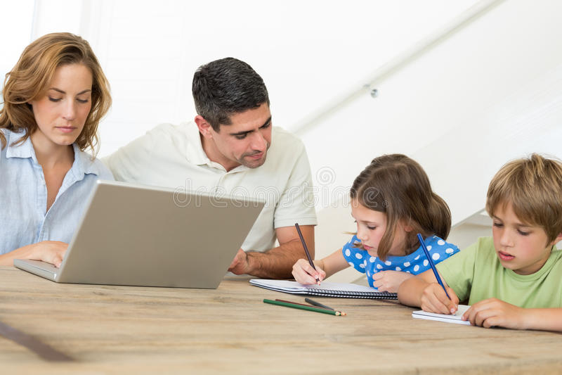 Mutter, Die Laptop Während Vater Unterstützt Kinder Bei Der Färbung ...