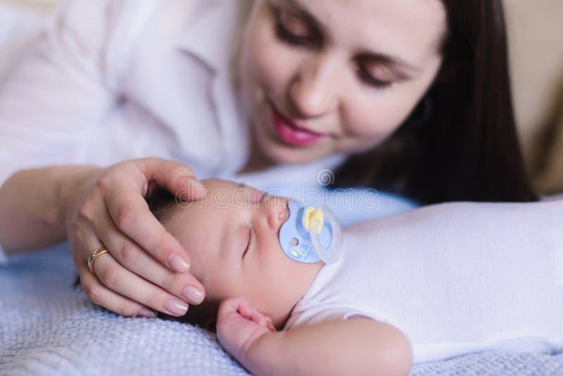 Mutter, die leicht den babys Kopf streicht lizenzfreies stockfoto