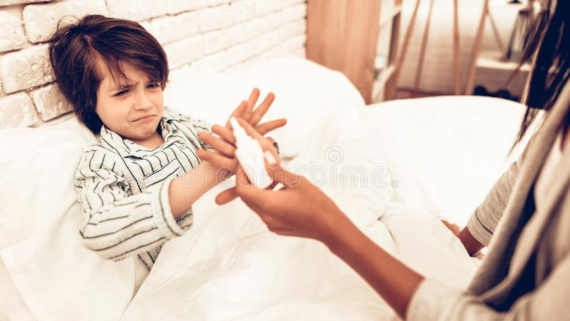 Mutter, die Medizin zu kranker Sohn-Lügenbett gibt stockbild