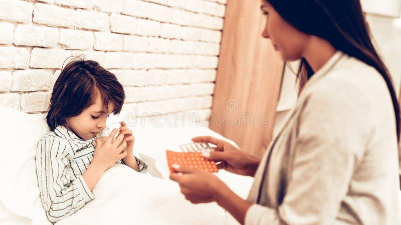 Mutter, die Medizin zu kranker Sohn-Lügenbett gibt lizenzfreie stockfotos