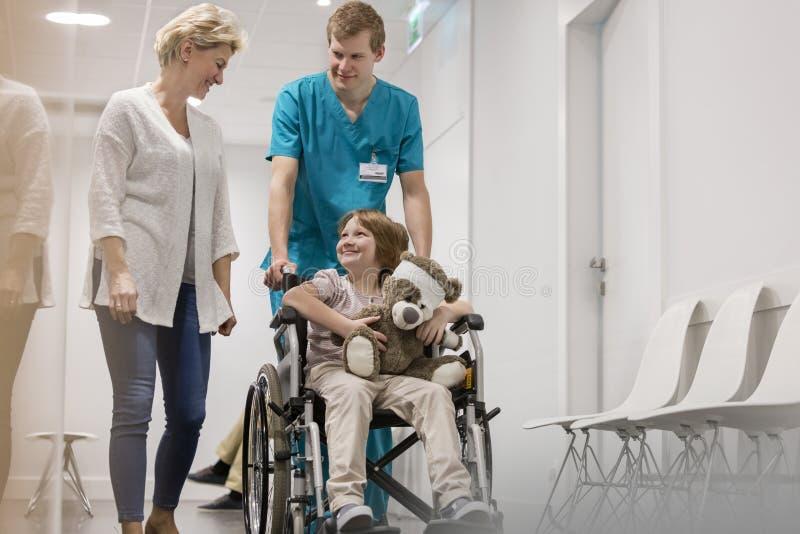 Mutter, die mit der Krankenschwester drückt kranken Jungen auf Rollstuhl im Krankenhauskorridor geht stockfotos