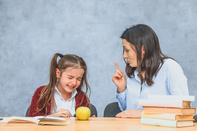 Mutter, die mit ihrem Baby spricht W?hrend dieses auf einem grauen Hintergrund Das Mädchen schreit, wenn ihre Mutter sie schweißt lizenzfreie stockfotografie