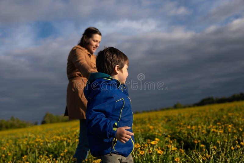 Mutter, die mit ihrem wenigen Sohn auf dem Feld geht lizenzfreie stockbilder