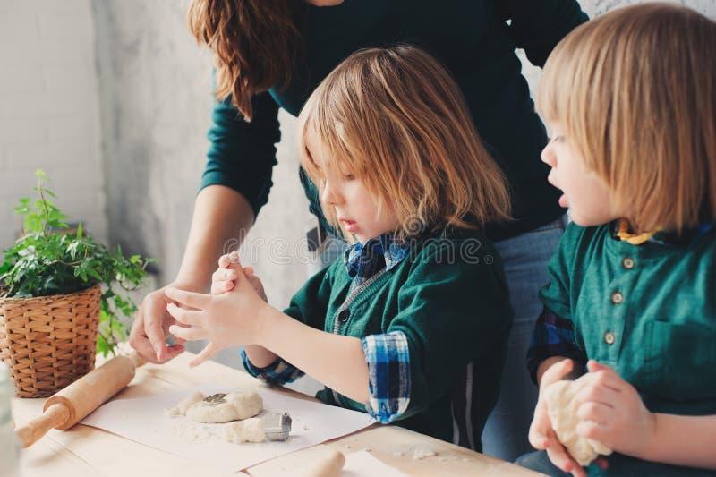 Mutter, die mit Kindern in der Küche kocht Kleinkindgeschwister, die zusammen backen und zu Hause mit Gebäck spielen stockbilder