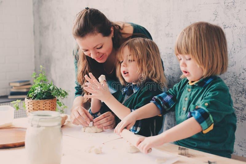 Mutter, die mit Kindern in der Küche kocht Kleinkindgeschwister, die zusammen backen und zu Hause mit Gebäck spielen lizenzfreies stockfoto