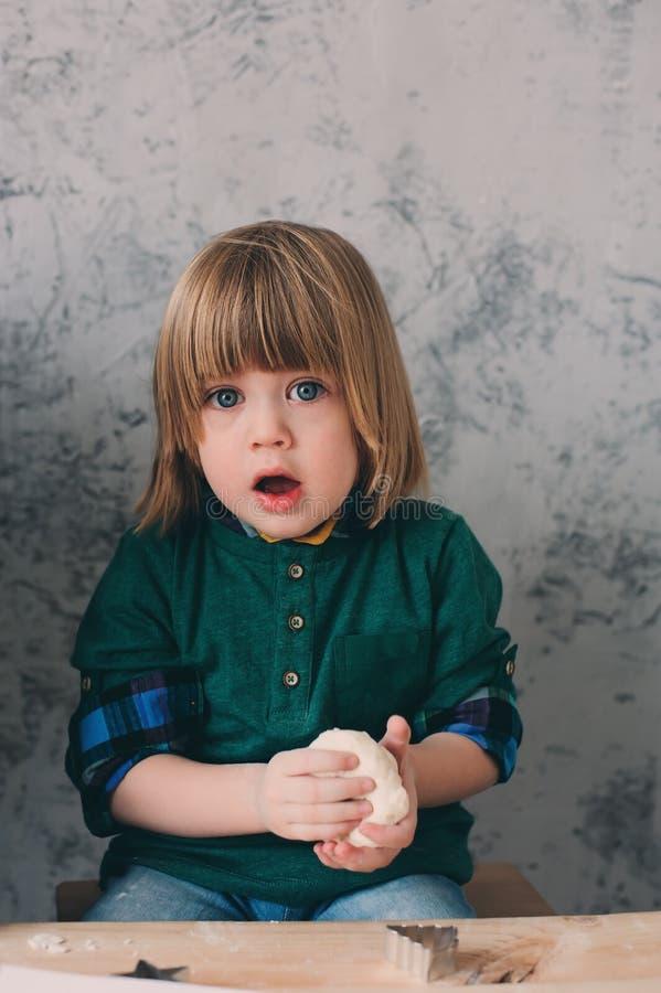 Mutter, die mit Kindern in der Küche kocht Kleinkindgeschwister, die zusammen backen und zu Hause mit Gebäck spielen lizenzfreie stockfotografie