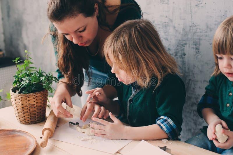 Mutter, die mit Kindern in der Küche kocht Kleinkindgeschwister, die zusammen backen und zu Hause mit Gebäck spielen lizenzfreie stockbilder