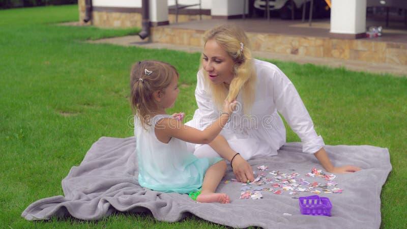 Mutter, die mit kleinem blondem Mädchen spielt stockfotos