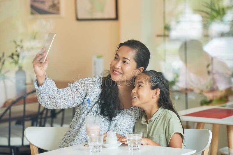 Mutter, die mit Tochter fotografiert lizenzfreie stockbilder