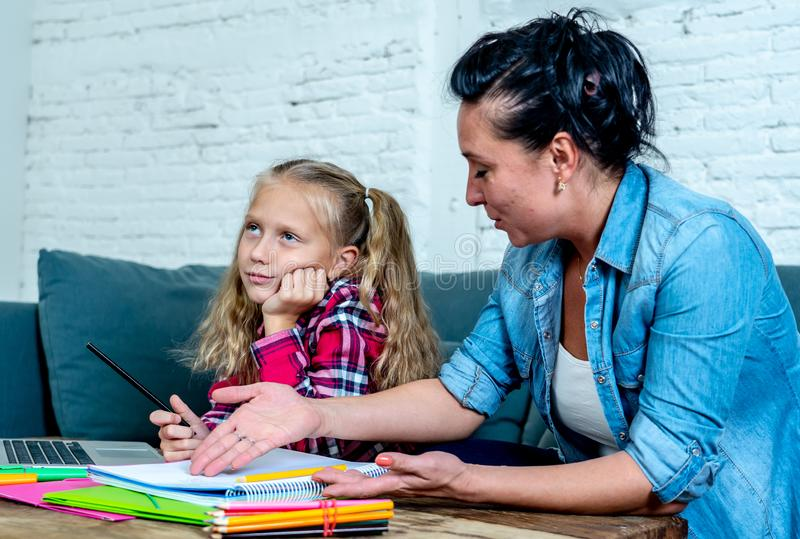 Mutter, die mit Tochter frustriert wird, während, die Hausarbeit tuend, die zu Hause auf Sofa bei der Lernschwierigkeitenhausarbe stockfoto