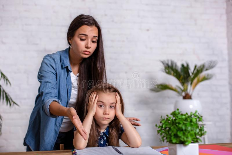 Mutter, die mit Tochter frustriert wird, während, die Hausarbeit tuend, die zu Hause am Tisch in den Lernschwierigkeiten sitzt lizenzfreie stockbilder
