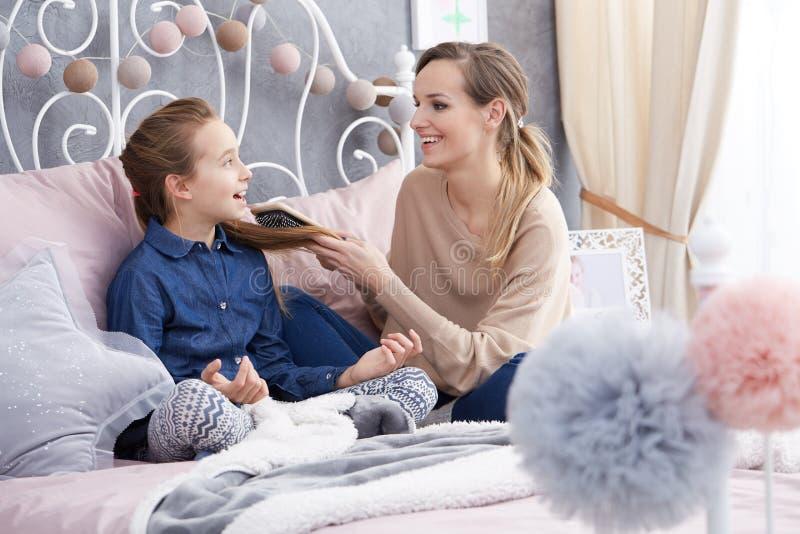 Mutter, die mit Tochter ` s Haar spielt stockfotografie