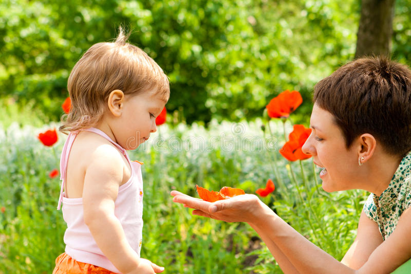 Mutter, die Mohnblumeblume zeigt lizenzfreies stockbild