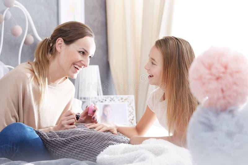 Mutter, die Nagellack anwendet lizenzfreie stockbilder