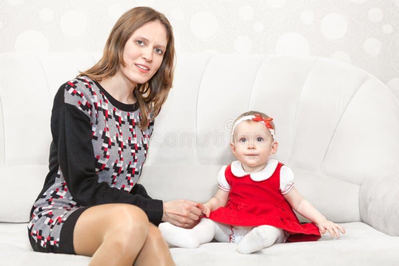 Mutter, die nahe Baby auf weißem Sofa sitzt lizenzfreie stockbilder