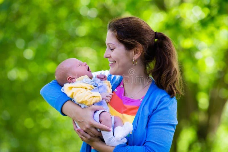 Mutter, die neugeborenes Baby in einem Park hält lizenzfreie stockfotos