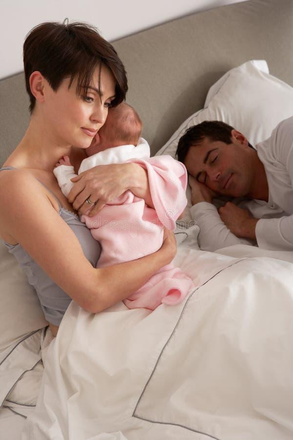 Mutter, die neugeborenes Schätzchen im Bett streichelt lizenzfreies stockbild