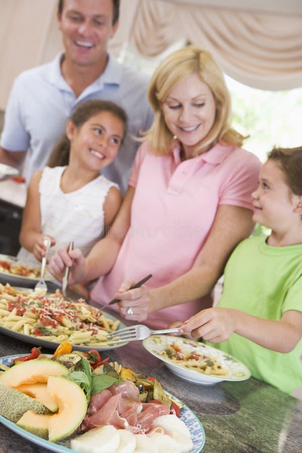 Mutter, die oben Abendessen für Familie dient lizenzfreie stockbilder