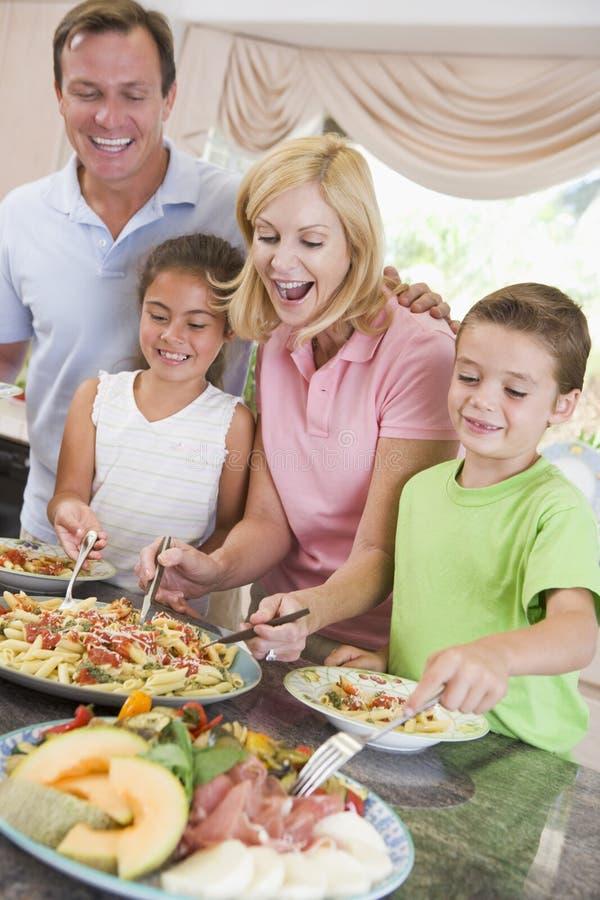 Mutter, die oben Abendessen für Familie dient stockfotos