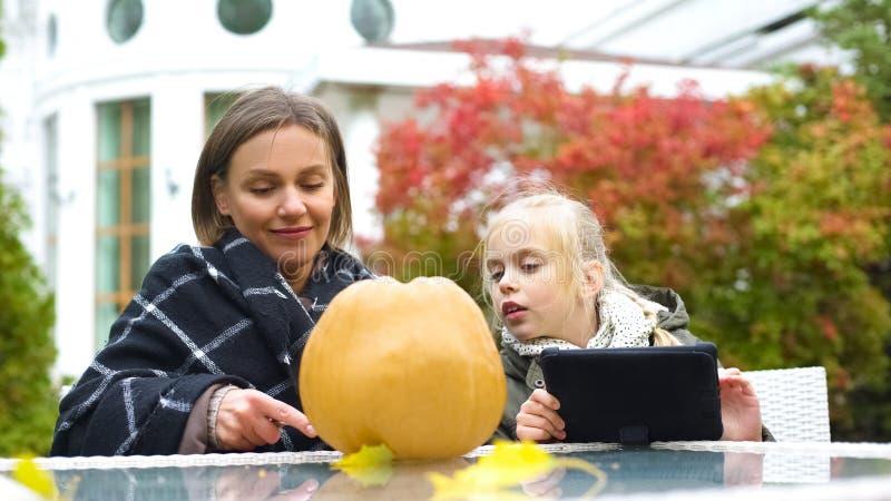 Mutter, die sorgfältig Kürbis während Tochter sucht nach Spitzen im Internet schnitzt lizenzfreie stockbilder