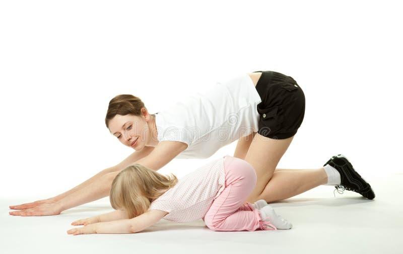 Mutter, die Sportübungen mit Tochter tut lizenzfreie stockbilder