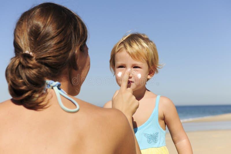 Mutter, die sunscream an ihrer Tochter anwendet stockfoto