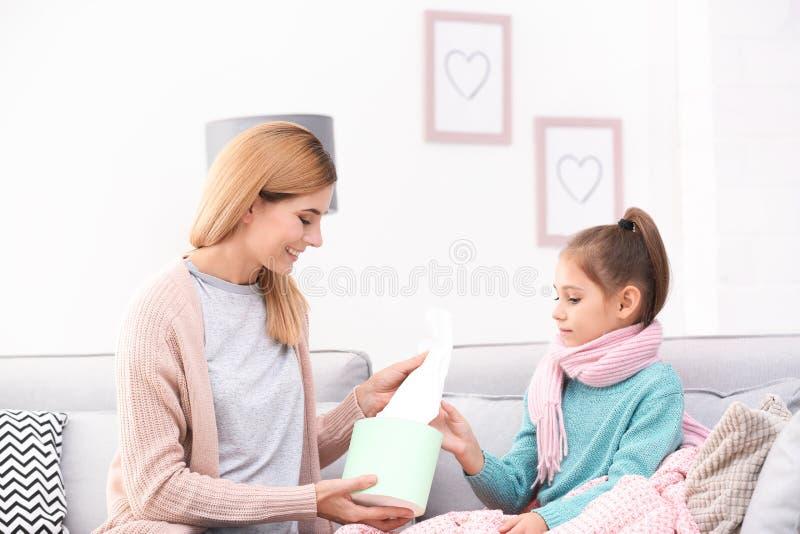Mutter, die Tochterpapiergewebe auf Sofa gibt lizenzfreies stockfoto