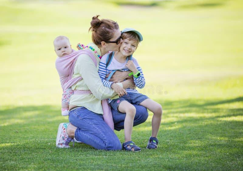 Mutter, die Vorschulsohn beim Tragen der Babytochter auf Rückseite in gesponnener Verpackung streichelt lizenzfreies stockbild