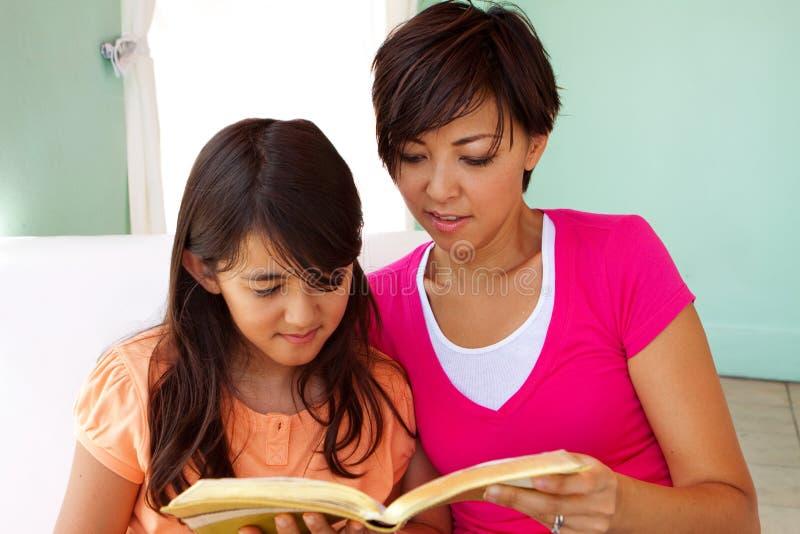 Mutter, die Zeitlesung mit ihren Töchtern ausgibt stockbilder