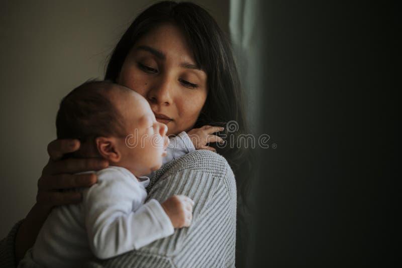 Mutter, die zuhause ihr Baby hält lizenzfreies stockbild