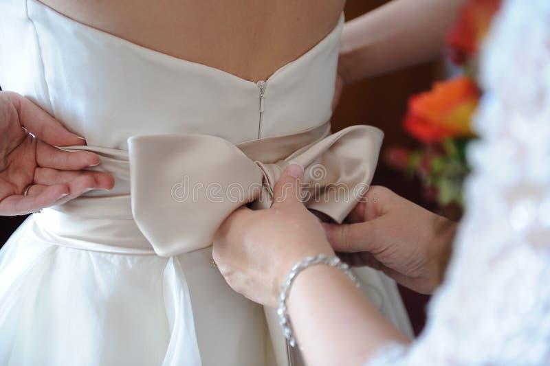 Mutter, die zurück vom Hochzeits-Kleid geraderichtet lizenzfreie stockbilder